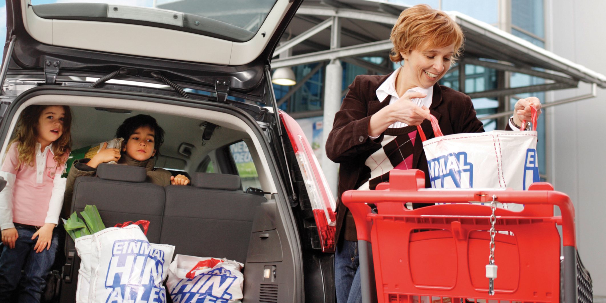 Customer with Kids loading Purchases into Car